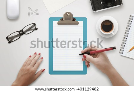 Female hand writing on notebook surrounded with office accessories. Top view of work desk. Coffee, glasses, pencil, mouse, paper, camera beside. - stock photo