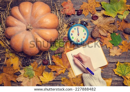Female hand writing something in notebook on autumn background.  - stock photo