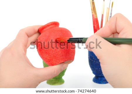 Female hands a brush paint a vase. Isolated on the white - stock photo