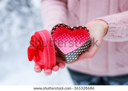 Female hands a gift box shaped of heart. Saint Valentine's day concept - stock photo