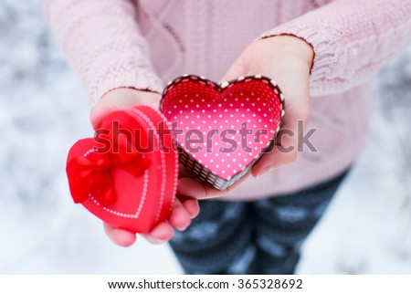 Female hands a gift box shaped of heart. Saint Valentine's day concept