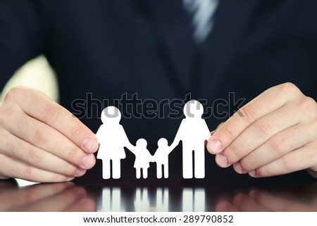 Female hands and chain family on wooden table, closeup - stock photo