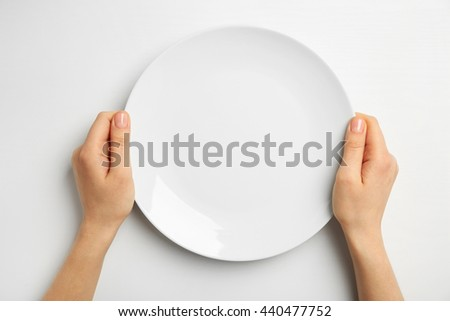 Female hands and empty plate isolated on white - stock photo