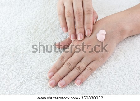 Female hands applaing a cream on fabric background