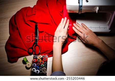 Female hands at work on sewing machine, closeup, top view. - stock photo