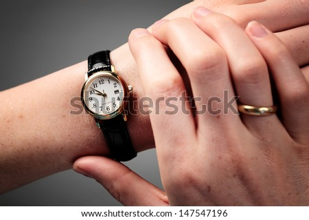 Female hands checking the time on a wristwatch. - stock photo