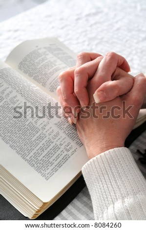 Female hands clasped in prayer over a Bible - stock photo
