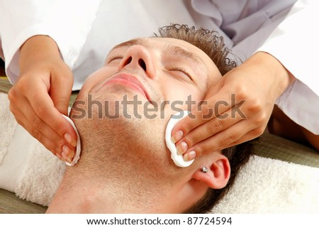 Female hands cleaning man's face with cotton swabs in a spa center - stock photo