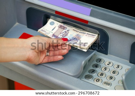 Female hands closeup with Russian rubles - woman withdraw money at cashpoints - stock photo