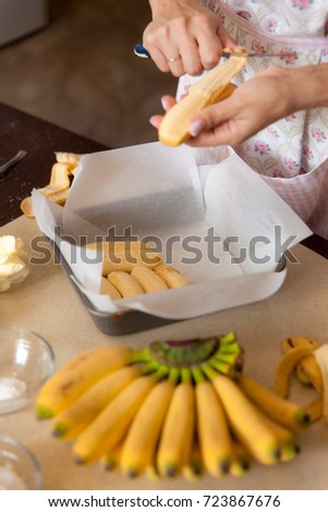 Female hands cut bananas for the pie. Cooking process on kitchen. Ingredients for sweet fruit dessert on table.