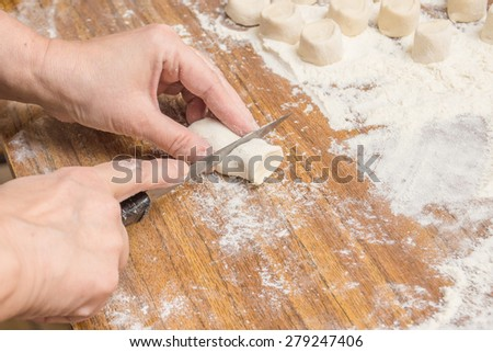 Female hands cut the dough for making dumplings - stock photo