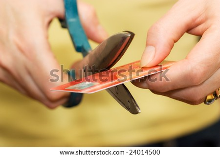 Female hands cutting a credit card - Control home budget - stock photo