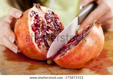Female hands Cutting pomegranate in a kitchen. Close-up. Selective Focus. - stock photo