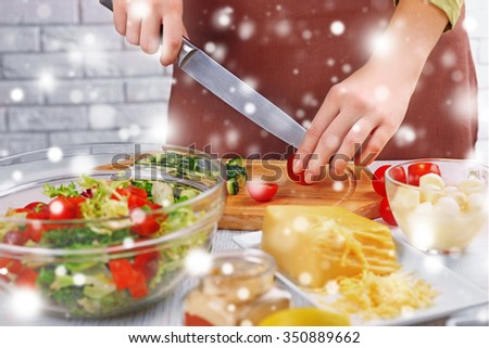 Female hands cutting vegetables for salad over snow effect - stock photo