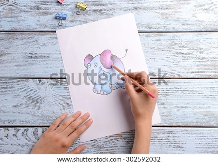 Female hands drawing elephant on sheet of paper on wooden table background - stock photo