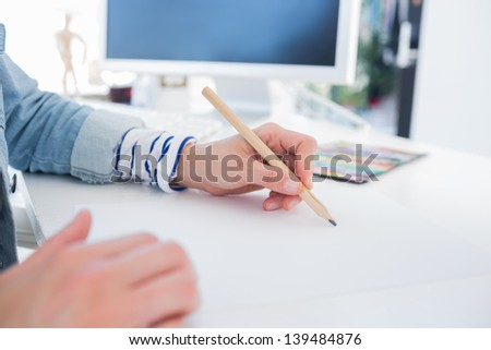 Female hands drawing on paper on her desk - stock photo