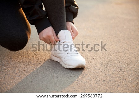 Female hands fixing laces on white sneakers in warm light on concrete, jogger preparing for running practice, close-up. Healthy, active lifestyle concepts, copy space - stock photo