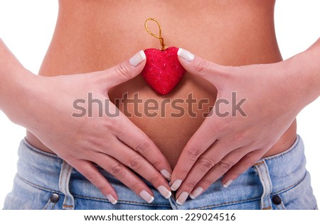 Female hands forming heart shape on the stomach isolated on white background  - stock photo