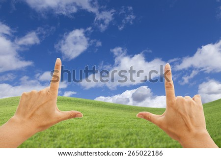 Female Hands Framing Beautiful Deep Blue Sky Above Lush Green Grass Field. - stock photo