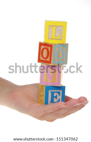 Female hands hold children's blocks with the word love