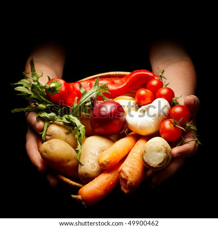 female hands holding a basket full of vegetables isolated on black - stock photo