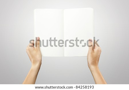 Female hands holding a blank white notebook. On a grey background - stock photo