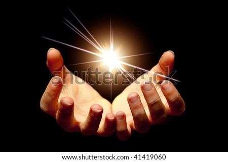 Female hands holding a brilliant star in the dark - stock photo