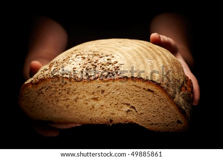 female hands holding a brown loaf of bread isolated on black