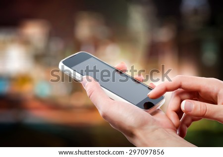 Female hands holding a cell phone (smartphone) with tuchscreen in night - stock photo