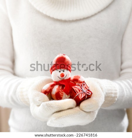 Female hands holding a cute happy Snowman. Woman hands in teal mittens showing a Snowman gift dresses in red hat and scarf. Cute Christmas present. Winter holidays concept. - stock photo