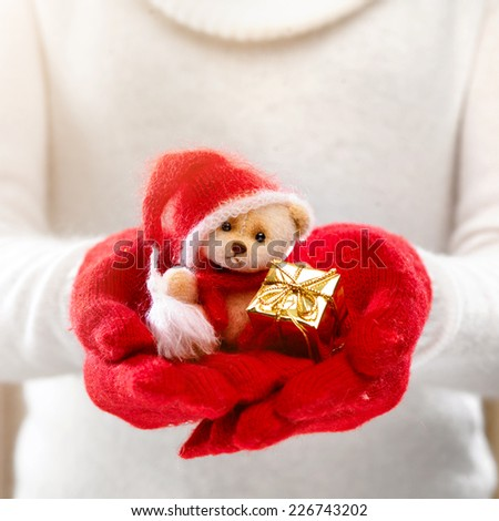 Female hands holding a cute teddy bear. Woman hands in red mittens showing a teddy bear gift dresses in knitted hat and scarf. Cute Christmas present. Winter holidays concept.  - stock photo