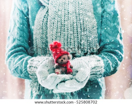 Female hands holding a cute teddy bear. Woman hands in teal mittens showing a teddy bear gift dresses in knitted hat and scarf. Cute Christmas present. Winter holidays concept