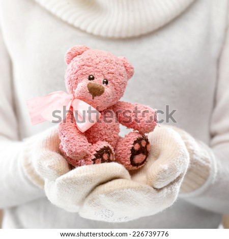 Female hands holding a cute teddy bear. Woman hands in white mittens showing a teddy bear gift dresses in  knitted hat and scarf. Cute Christmas present. Winter holidays concept.  - stock photo