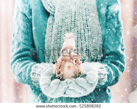 Female hands holding a cute White snowman. Woman hands in teal mittens showing a snowman gift dresses in pink knitted hat and scarf. Cute Christmas present. Winter holidays concept