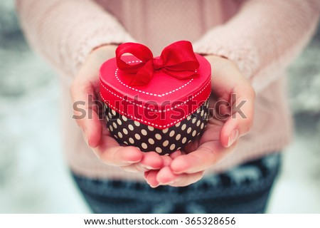 Female hands holding a gift box shaped of heart. Saint Valentine's day concept. Toned picture - stock photo