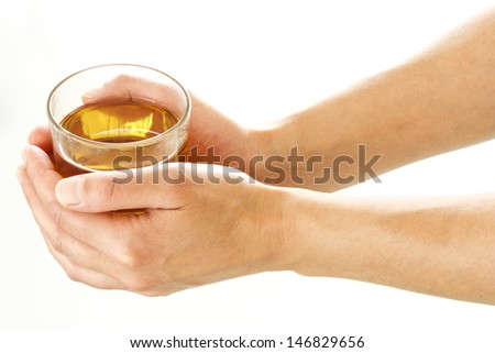 Female hands holding a glass of tea over a white background - stock photo