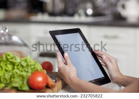 female hands holding a laptop at the dining table in the kitchen - stock photo