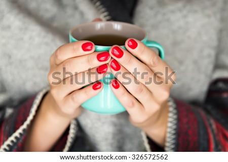 female hands holding a mug of hot tea - stock photo