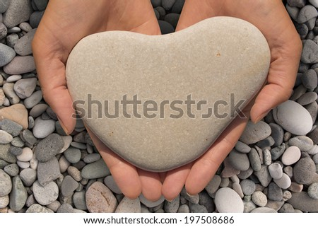 Female hands holding a natural heart-shaped stone in cupped palms over a background of water worn pebbles - stock photo