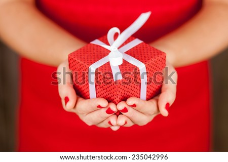 Female hands holding a present box - stock photo