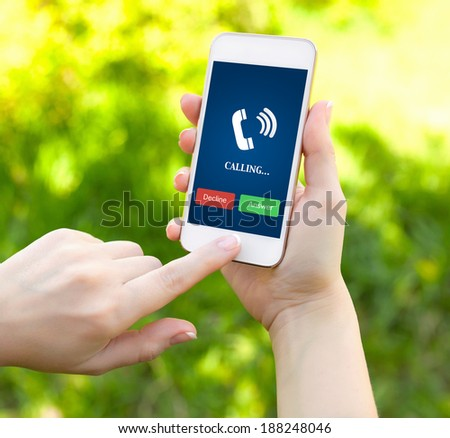 female hands holding a white phone with ringing tube on the screen on a background of green grass - stock photo