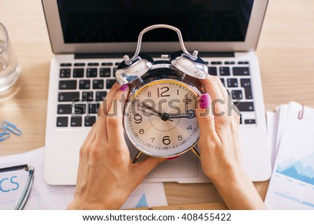 Female hands holding alarm clock over desktop with laptop and other items - stock photo