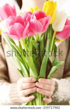 Female hands holding beautiful colorful tulips. Tuned image - stock photo