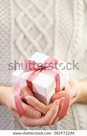 Female hands holding beautiful small gift wrapped with satin ribbon. - stock photo