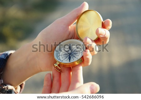 Female hands holding compass on blurred countryside road background