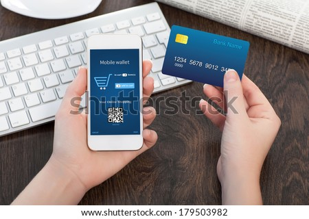 female hands holding credit card and a touch phone on the table in the office and making a purchase onlain  - stock photo