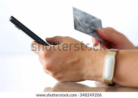 Female hands holding credit card and making online purchase using mobile phone. Shopping, consumerism, delivery or internet banking concept. Anti-fraud and financial security concept