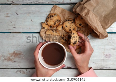 Female hands holding cup of coffee and cookies on wooden table close up - stock photo