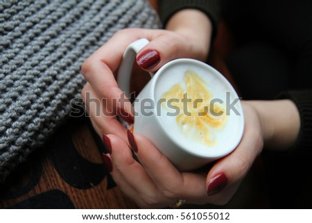 Female hands holding cup of Coffee in Coffee shop.