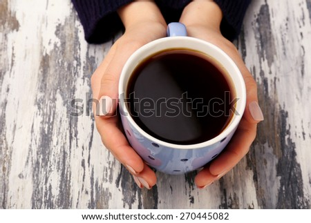 Female hands holding cup of coffee on wooden background - stock photo